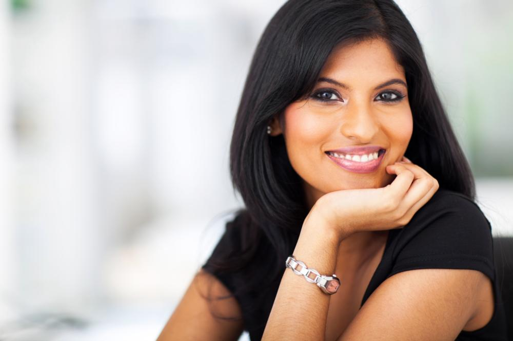 Woman smiling and resting head on her hand | Cosmetic Dentist Bangor ME