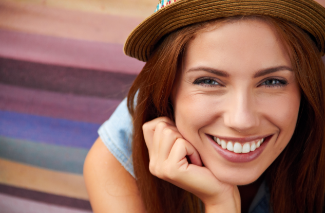 woman smiling with her hand on her chin wearing a hat