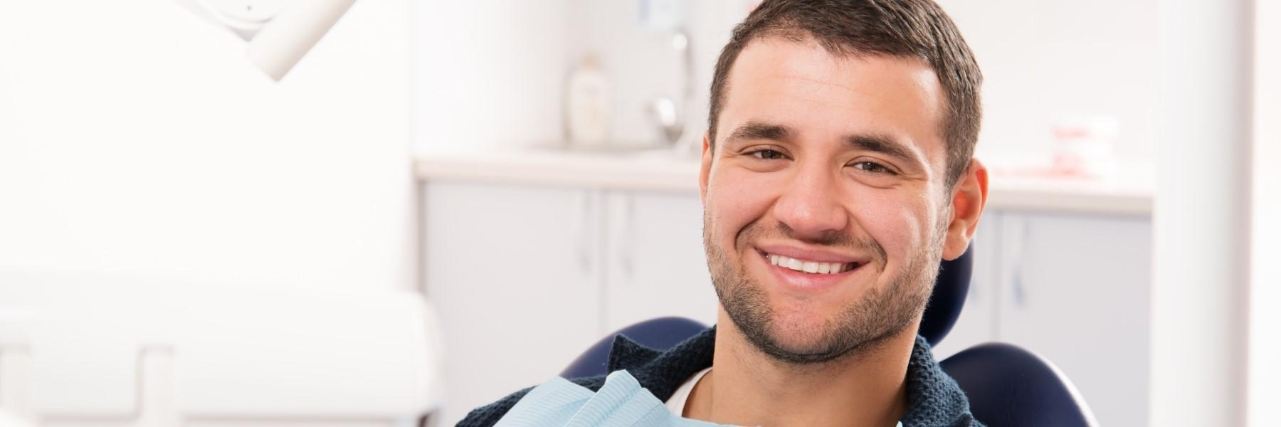 man smiling in the dental chair wearing a bib