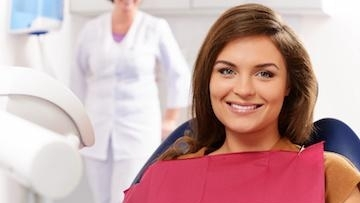 woman smiling in the dental chair wearing a red bib
